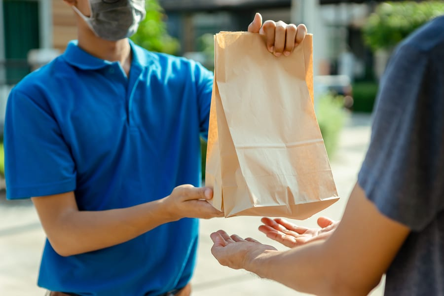 man in mask deliver food from online ordering