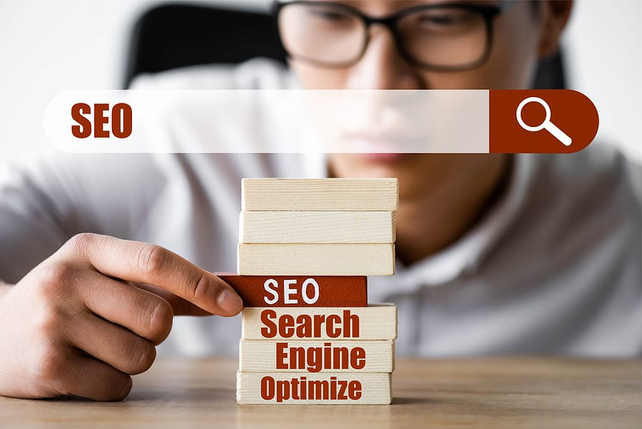 SEO blocks and search bar, selective focus of man touching the blocks