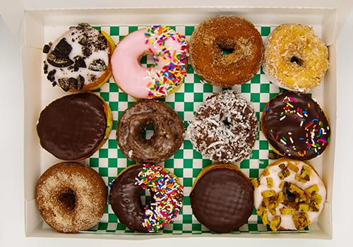 product photography of a dozen donuts in a box