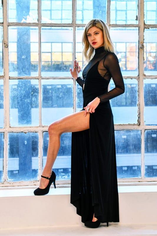 JoJo - blonde model showing of leg in front of window