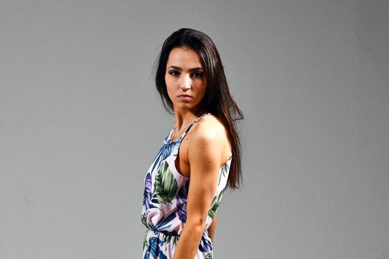 Kitti - Burnette model in floral dress on grey background