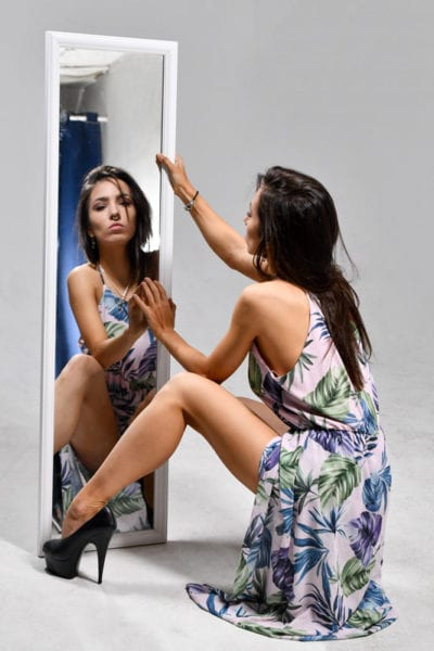 Kitti - brunette model looking at her reflection in the mirror