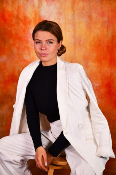 Leah - redhead model in black with white jacket, orange background