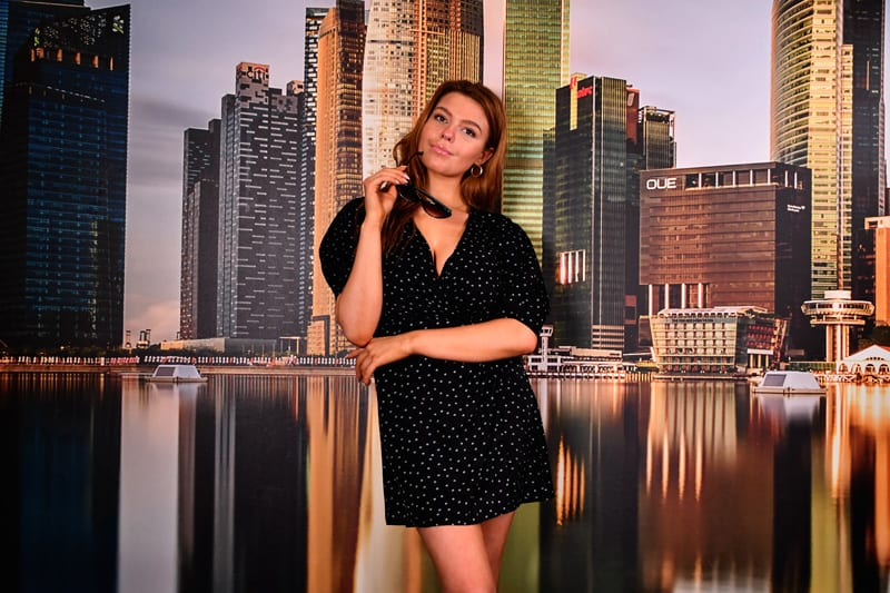 Leah models - redhead model in front of cityscape background in dark dress