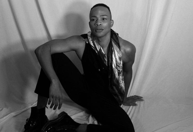 Model - Shaun - tall black man sitting on floor in black and white