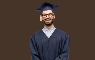 family photo - male graduate on brown backdrop