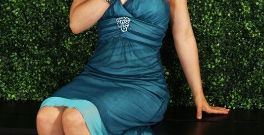 Aubrey - redhead model in blue dress against green backdrop
