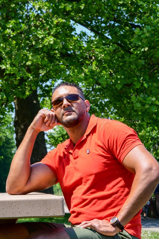 male model in red polo sitting at a table in the park