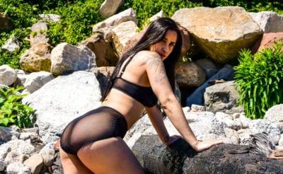 model elena leaning on wooden pole on beach in lingerie