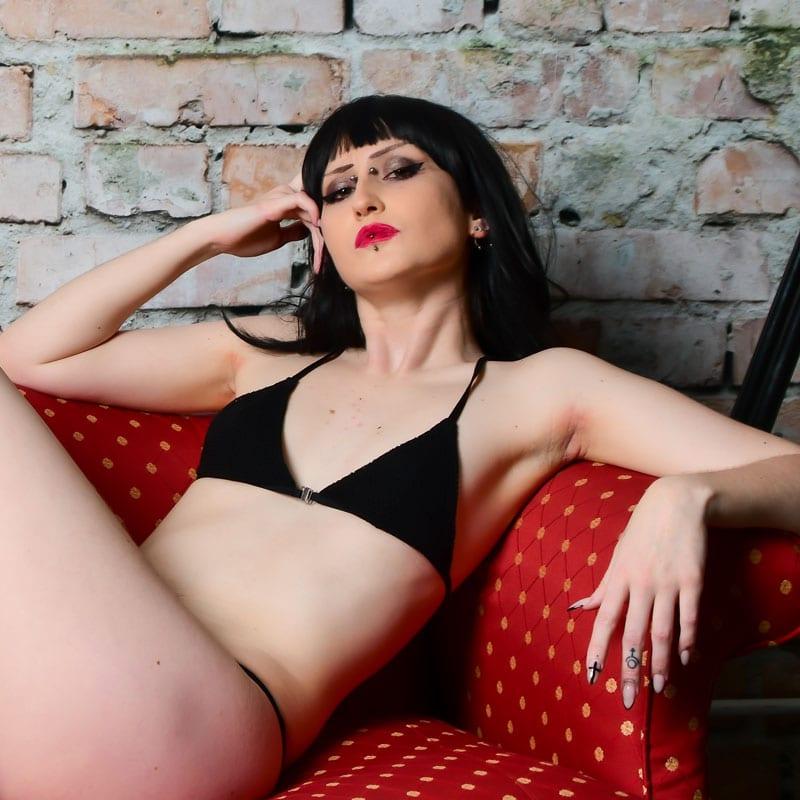 Dark-haired model on couch, goth model jynx