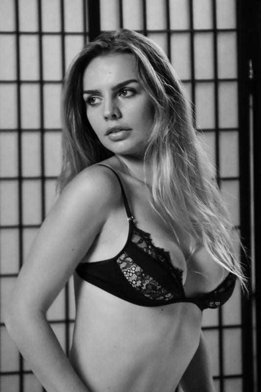 Blonde model on bed in lingerie black and white