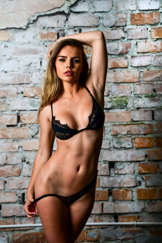 Blonde model in front of distressed brick wall in lingerie