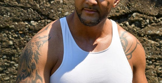male model in white tank top in front of stone